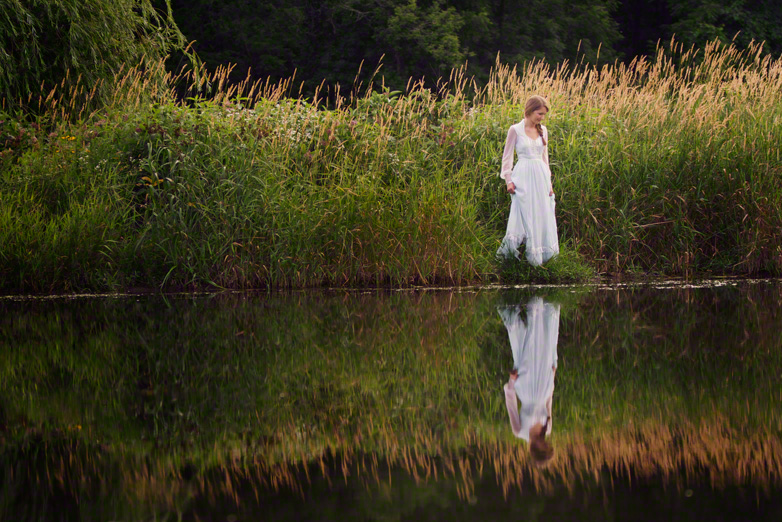 Senior teen in vintage dress reflected on water