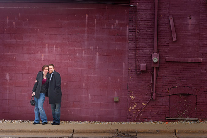 Engaged couple in front of wall
