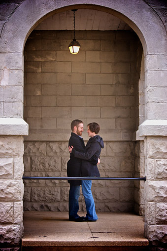Engaged couple embracing in stone archway