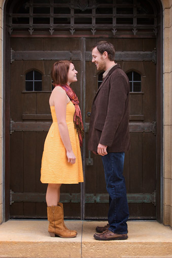 Engaged couple in front of old door. Woman wearing a trendy yellow dress & man a blazer