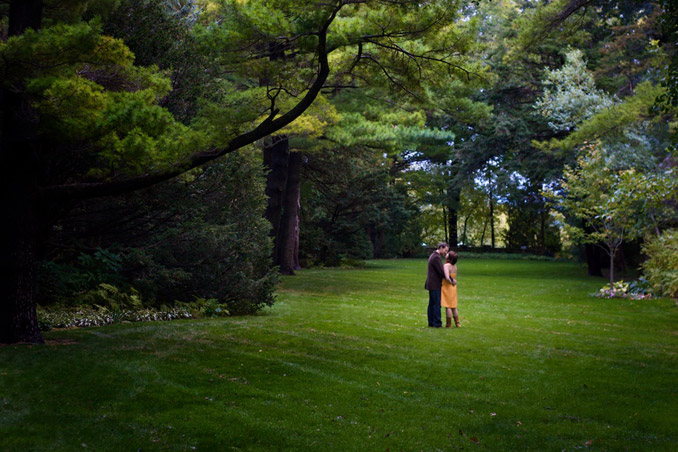 Engaged couple in open, manecured lawn with trees towering around the edges