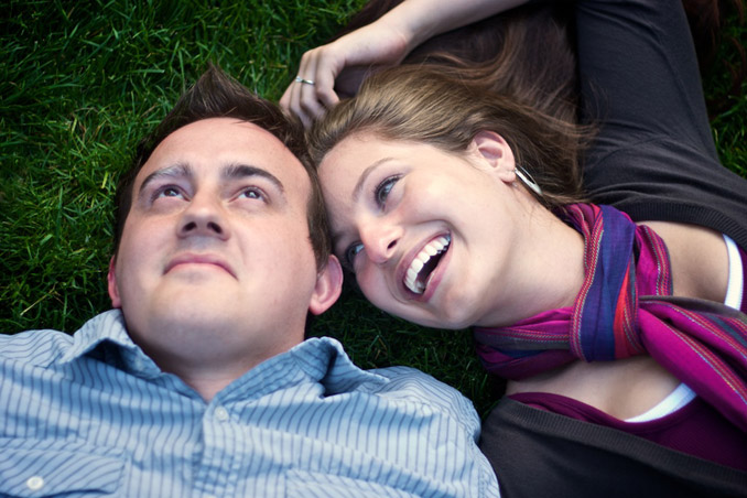 Engaged couple in grass laughing