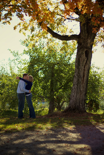 Engaged couple kissing under tree in apple orchard