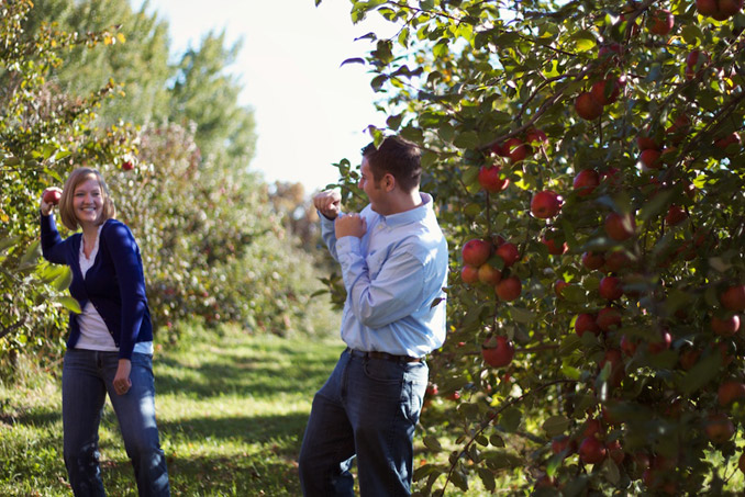 Engaged couple playing, woman throwing apple at fiancé