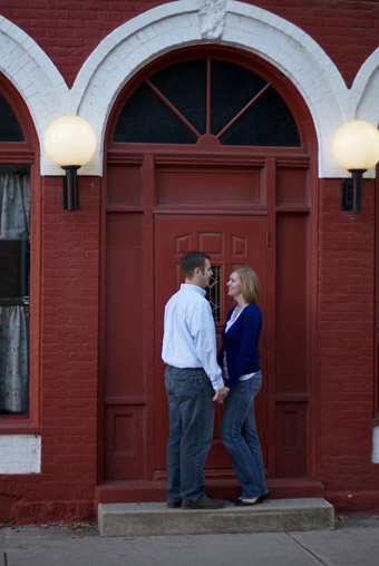 Engaged couple in front of old red building with arched doorway