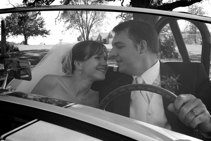 Black and white photo of bride and groom in front seat of sports car