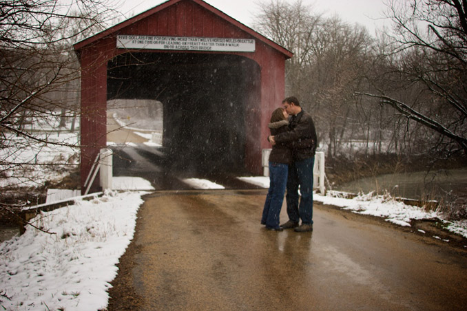 Engaged couple kissing near snowy red covered bridge