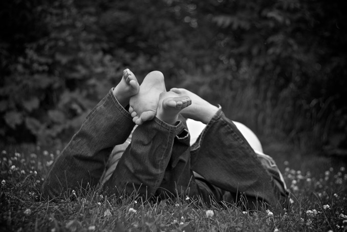 Black and white photo of engaged couple laying in the grass feet toward the camera