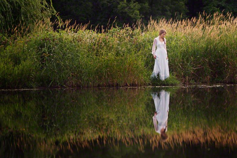 Senior teen in vintage dress reflected on water