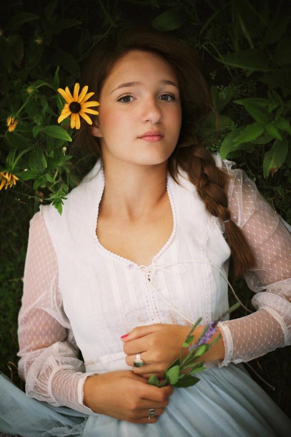 Senior teen girl laying in grass