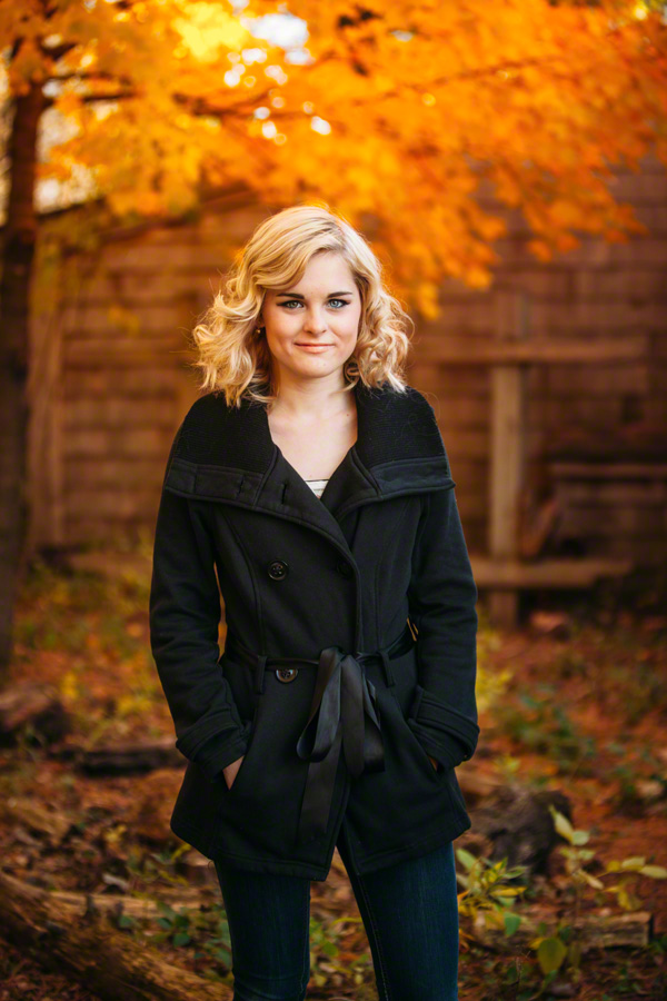 Senior with fiery fall leaves behind