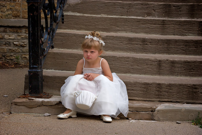 Cute flower girl moping because the ceremony is over