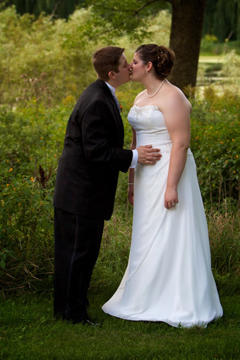 Portrait of Bride and Groom kissing outdoors