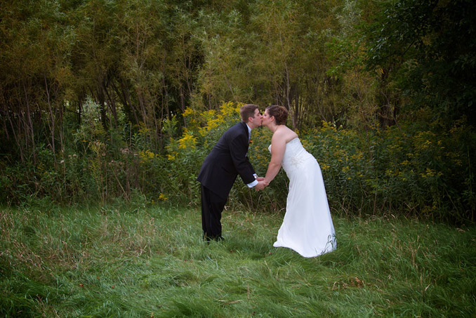 Outdoor portrait of bride and groom stooped over to kiss each other