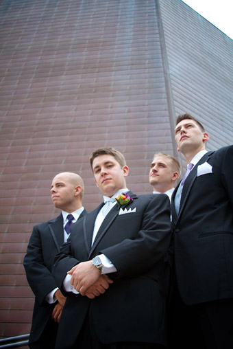 Upward look at groomsmen in cool pose in front of retro wall