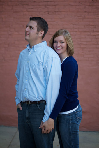 Engaged couple in front of brick wall