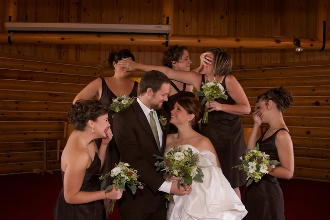 Humorous pose with bride, groom, and bridesmaids; bride and groom gazing happily at each other while the bridesmades look away in discust.