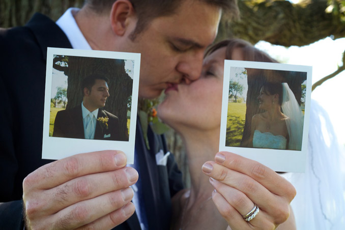 Bride and groom holding polaroids of themselves while kissing out of focus