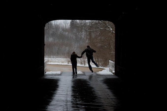 Silhouette of couple in opening of a covered bridge. Man is kicking his heels.