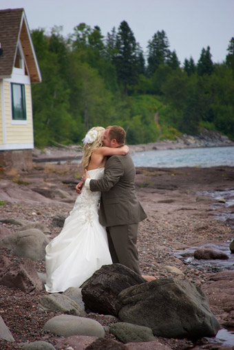 Bride and groom embrasing on shoreline after their first-look