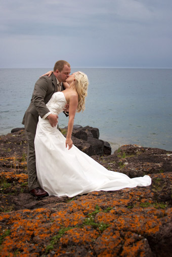 Wedding couple dipping to kiss on rocky shoreline of Lake Superior