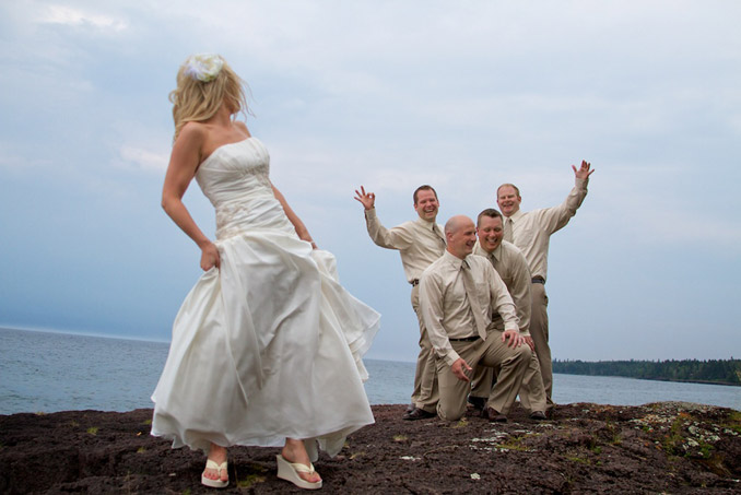 Bride looking back over shoulder at groomsmen on rocky coastline of Lake Superior