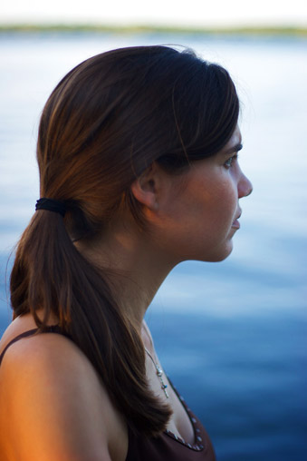 woman looking out over deep blue lake
